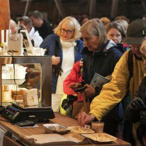 En kvinna säljer ost åt några kunder vid en disk.