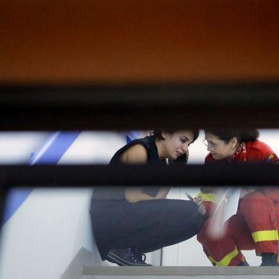 Ensihoitaja rauhoittelee yökerhopalon uhrin omaista sairaalan käytävällä Bukarestissa, Romaniassa.