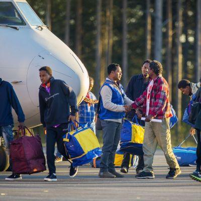 Eritrealaisia turvapaikanhakijoita Luulajan lentokentällä lentokoneen edustalla.