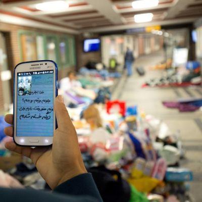 Poika katsoo kännykkää, jonka näytöllä on tekstiä.