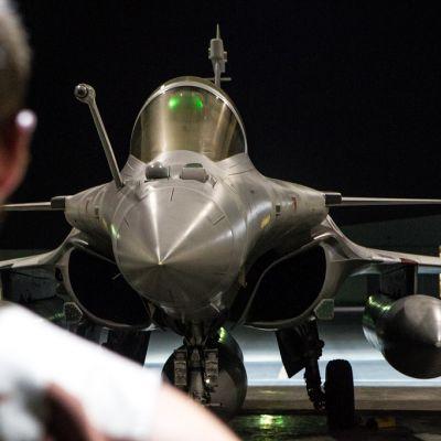 Sotilas seisoo mustan hävittäjäkoneen edessä.