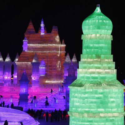 Kuva lumesta ja jäästä rakennetuista linnoista yövalaistuksessa. Taivas on täysin musta. Edustalla loistaa vihreänä jäälinnan torni, taustalla punaisissa ja violeteissa väreissä suuri lumilinna. Ihmisiä näkyy kävelemässä linnan portailla pieninä mustina hahmoina.