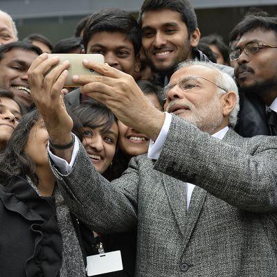 Intian pääministeri näyttää esimerkkiä selfien ottamiseen. Intialaisia opiskelijoita on paljon hänen ympärillään.