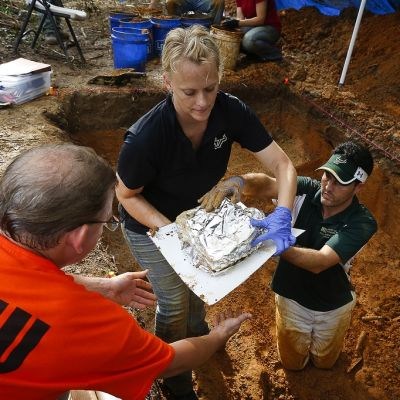 Kahden miehen avustama Kimmerle nostaa hautakuopasta folioon käärittyjä jäänteitä.