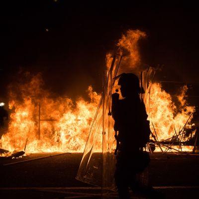 Mellakkavarusteisiin pukeutunut poliisi seisoo mielenosoittajien sytyttymän tulipalon edessä.