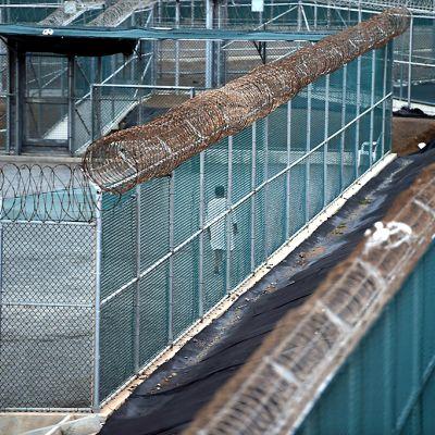 Valkopukuinen vanki kävelee Guantánamon vankileirin pihamaalla.
