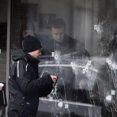 Poliisit tutkivat Kööpenhaminan ammuskelun jälkiä kulttuuritalon ovessa.