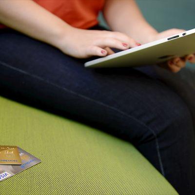 Nainen tarkistaa luottokorttinsa numeron tehdessään nettiostoksia vihreällä sohvalla.