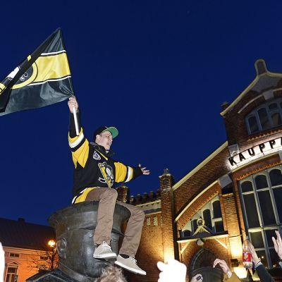 Mies istuu patsaan päässä lippu kädessä.