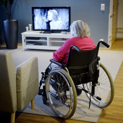 Hoitokodin asukas istuu pyörätuolissa ja katsoo televisiota.
