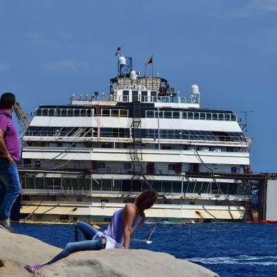 Ihmisiä rannalla Costa Concordia -aluksen edustalla Giglion saarella 13. heinäkuuta 2014.