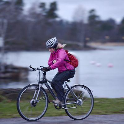 Pyöräilijä puskee tuulta vasten Helsingissä.
