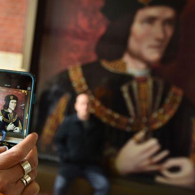 Nainen ottamassa valokuvaa Rikhard III:sta esittävästä julisteesta Leicesterin katedraalissa, Englannissa 23. maaliskuuta.