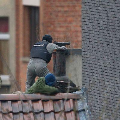 Kolme poliisia katonharjalla. Kaksi tähtää aseella, kolmas kiikaroi.