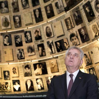 Tomislav Nikolić katsoo ylöspäin huoneessa, jonka seinillä on ihmisten valokuvia ja tekstejä.