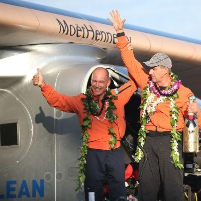 Kaksi iloista lentäjää  kukkaseppeleet kaulassa ja sampanjapullo kädessä viittoilee lentokoneen edessä.