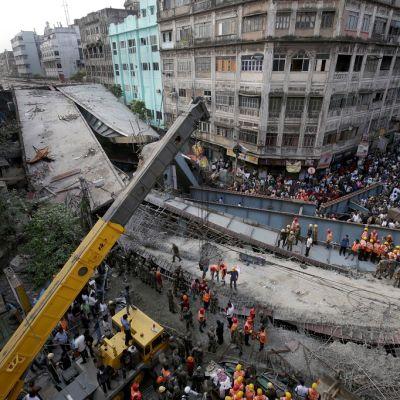 Ihmisiä parveilee kadulla romahtaneen sillan vieressä.