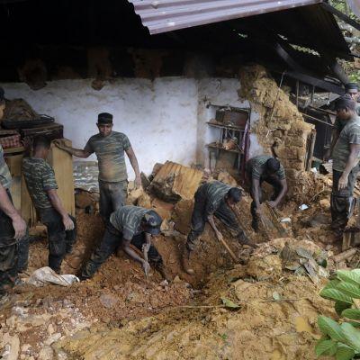 Joukko sotilaita kaivaa maata talon seinustalla.