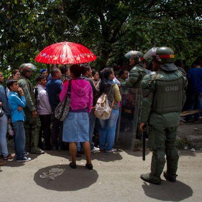 Joukko ihmisiä seisoo jonossa puiden varjossa. Yhdellä jonottajalla on auki kirkkaanpunainen sateenvarjo. Kansalliskaartin sotilaat valvovat jonoa.