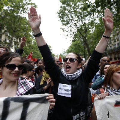 Kuva mielenosoituksesta. Joukko ihmisiä kantaa banderollia. Keskialalla palestiinalaishuiviin ja tummaan paitaan pukeutunut nainen pitää käsiään ylhäällä ja huutaa ilmeisesti jotain iskulausetta.
