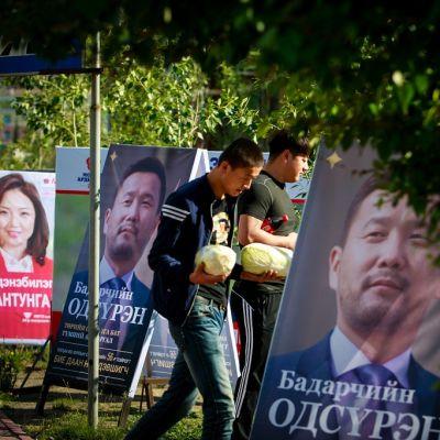 Kaksi miestä kulkee isojen mainostaulujen välistä puistossa.