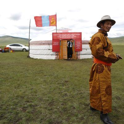 Koristeelliseen perinnetakkiin pukeutunut mies ruoholakeudelle pystytetyn teltan edessä. Teltan katolla liehuu Mongolian lippu.