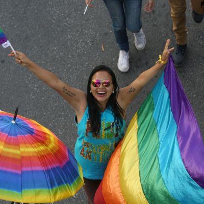 Sateenkaarilippua kannatteleva ja toisessa kädessä pienoislippua heilutteleva nuori nainen.