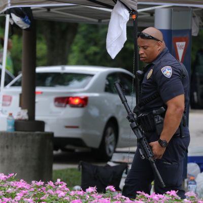 Aseistautunut poliisi, taustalla autoja.