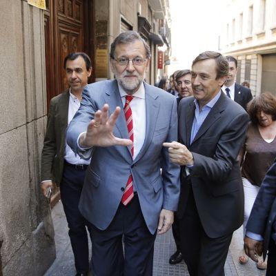 Rajoy katsoo kameraan ja elehtii kädellään pienen väkijoukon keskellä.
