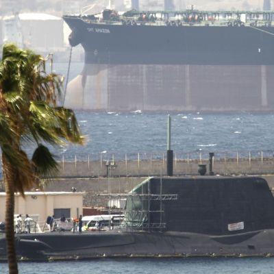 Sukellusvene betonilaiturissa. Edessä tuulen tuivertama palmu, takana iso rahtialus.