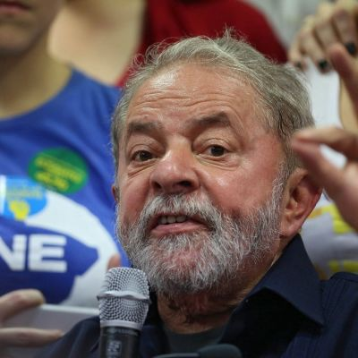 Parrakas Lula da Silva puhuu oikeassa kädessään olevaan mikrofoniin ja elehtii vasemmalla kädellään, jonka etusormi ja peukalo ovat yhdessä. Lulalla on tummansininen kauluspaita. Taustalla seisoo kannattajia.