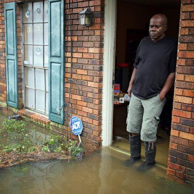 Mies saappaat jalassa kynnyksellä, vesi yltää jalkateriin asti.