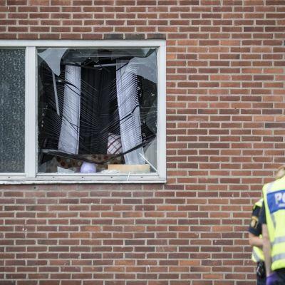 Kuva rikkoutuneesta ikkunasta. Sälekaihtimet ovat vääntyneet. Ulkopuolella kaksi poliisia.