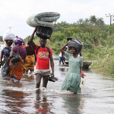 Joukko ihmisiä, jotka kävelevät vedessä pellon laidassa. He kantavat omaisuuttaan päänsä päällä.