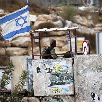 Betoninen vartiotorni, jonka yllä liehuu Israelin lippu.