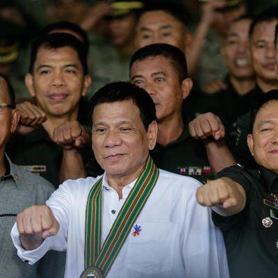 Presidentti Rodrigo Duterte ja joukko armeijan upseereita näyttävät nyrkkiä.