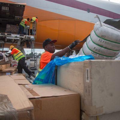 Ruoka-apusäkkejä lastataan lentokoneesta Haitissa.