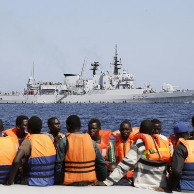 Pelastusliiveihin pukeutuneita miehiä laivan partaalla. Takana laivaston harmaa alus.