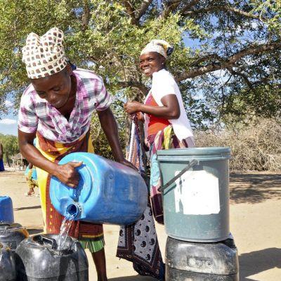 Naiset hakevat vettä säiliöihinsä. Taustalla tyttö seuraa tilannetta.