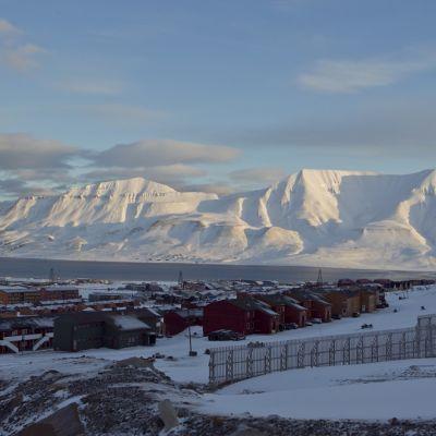 Etualalla kylän taloja, taustalla kaksi lumen peittämää vuorta.