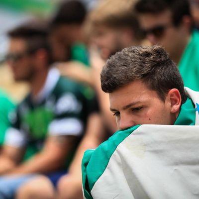 Sureva poika istuu stadionilla ja on kietoutunut valkovihreään jalkapallojoukkueen lippuu.n