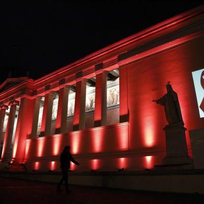 Ateenan yliopiston julkisivu on punainen aids-päivän kunniaksi.