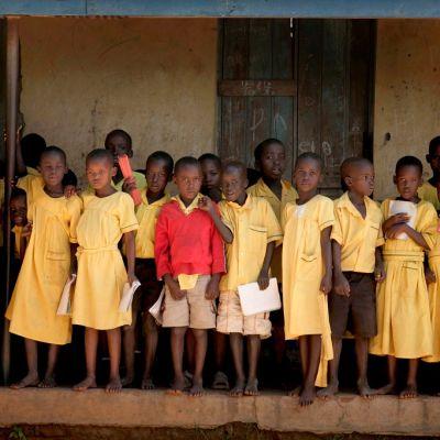 kelta-asuisia koululaisia seisoo katoksen alla.