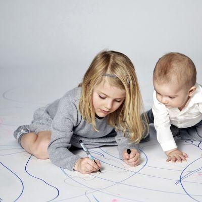Lapset kontallaan lattialla, Estelle piirtää ja Oscar katsoo vieressä. Lattia on peitetty valkoisella paperilla, joka on täynnä sinisellä piirrettyjä kuvioita.