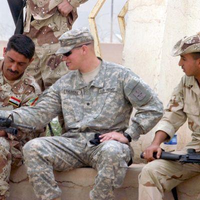 Irakilaisten sotilaiden välissä istuu amerikkalaissotilas, asetta tutkitaan