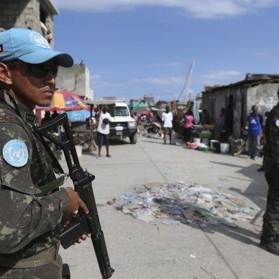 sSniset YK-lippikset miehillä päässä, aseet kädessä, kadulla Haitissa