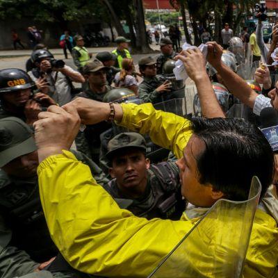 Mellakkavarusteisten kansalliskaartin sotilaiden rivistö estää mielenosoittajien pääsyn korkeimman oikeuden rakennukselle. Monet protestoijista ottavat kuvia kännykkäkameroillaan.