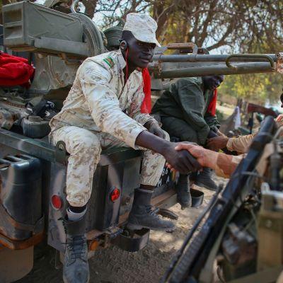 Malilaissotilas istuu auton päällä ja kättelee ranskalaissotilasta