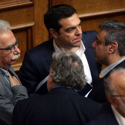 Kreikan pääministeri Alexis Tsipras odottaa äänestystulosta ministereiden keskellä.