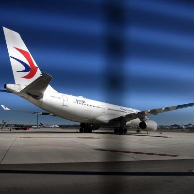 Lentokone kentällä kuvattuna aidan läpi.